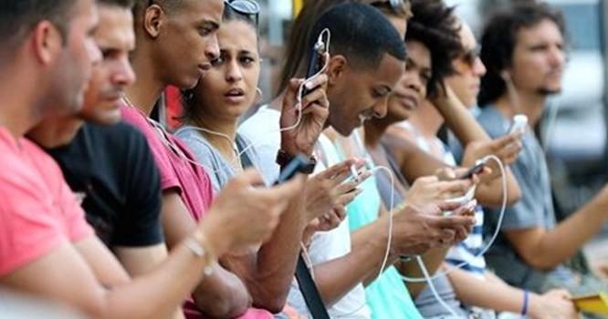 Người dân Cuba dùng điện thoại di động tại Havana. Ảnh: CNBC.
