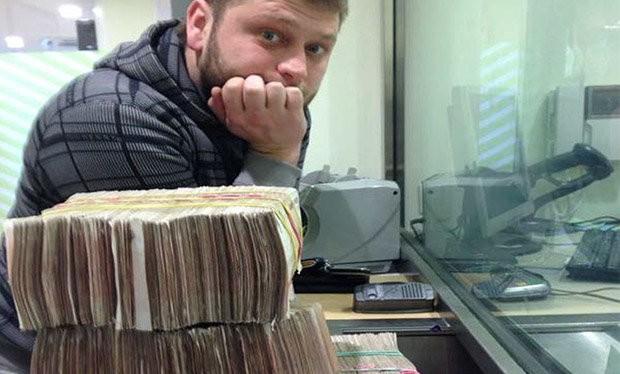 Hacker Seleznev với những cọc tiền bên cạnh chiếc máy tính xách tay của anh này vào thời điểm bị bắt tại Maldives năm 2014 - Ảnh: Bộ Tư pháp Mỹ