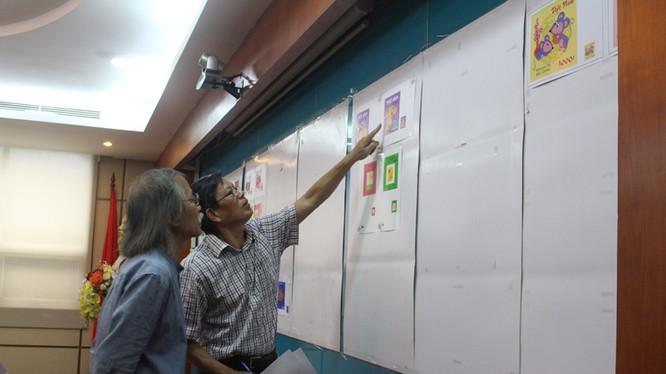 Các thành viên Hội đồng chấm thi xem xét, đánh giá và lựa chọn các mẫu tem Tết. Ảnh: MIC.gov.vn