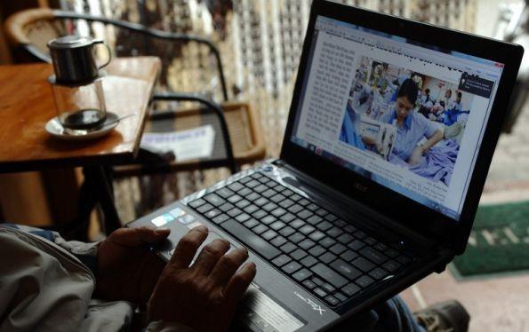 Một người đàn ông đang đọc tin trên mạng bằng laptop trong một quán cafe ở Hà Nội. Ảnh minh hoạ: AFP