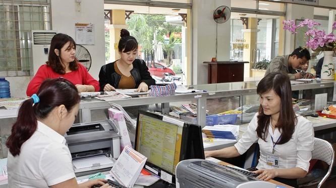 Giao dịch viên phục vụ khách hàng từ mùng Ba Tết. Ảnh: Minh Đàm