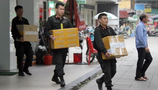 Khám xét chuỗi cửa hàng Nhật Cường, cảnh sát thu giữ hàng nghìn điện thoại, tài liệu liên quan. Ảnh: Hoàng Lam.