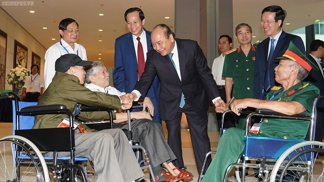 Thủ tướng thăm hỏi các đồng chí thương binh nặng tới dự buổi gặp mặt.