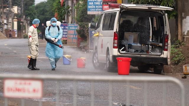 Lực lượng chức năng phun khử khuẩn phía trước ngôi nhà bệnh nhân 243. Ảnh: CDC Hà Nội.