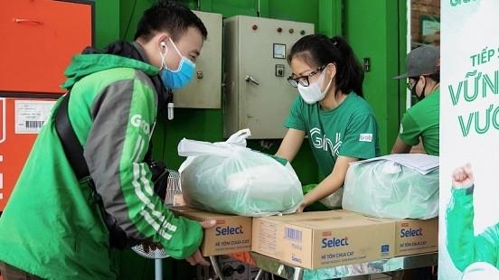 Bà Nguyễn Thái Hải Vân - Giám đốc Điều hành, Grab Việt Nam - tặng gạo và mì cho đối tác tài xế. Ảnh: Grab cung cấp.