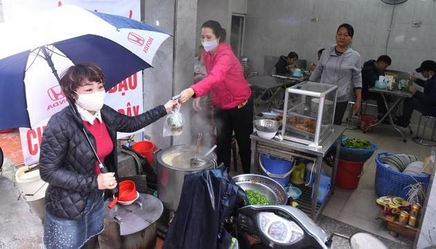 Người kinh doanh thức ăn đường phố phải đeo khẩu trang khi tiếp xúc với thực phẩm, giữ khoảng cách với khách. Ảnh: Bộ Y tế