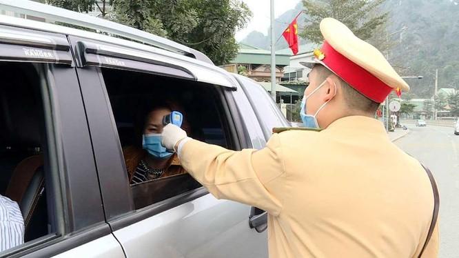 Công an TP Cẩm Phả vừa điều tiết giao thông vừa kết hợp với đo nhiệt độ người tham gia giao thông. Ảnh: UBND tỉnh Quảng Ninh.