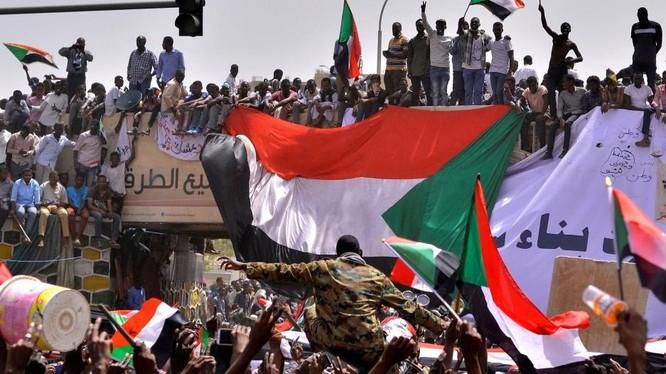 Một sĩ quan quân đội đứng giữa đám đông người biểu tình ở Thủ đô Khartoum, Sudan (Ảnh: Reuters)
