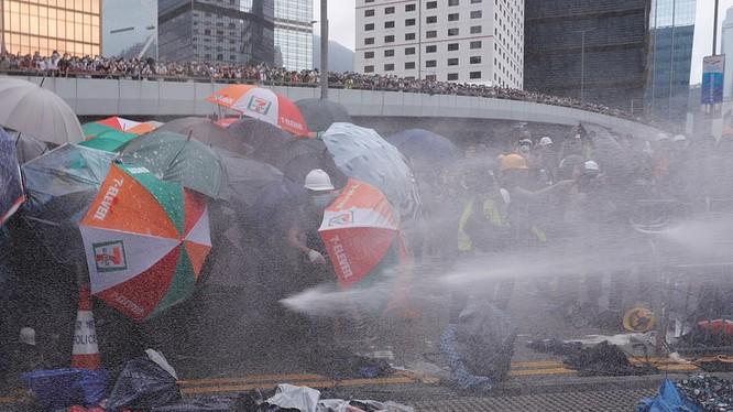 Người biểu tình dùng ô như lá chắn trong lúc tìm đường tiến vào tòa nhà Nghị viện (Ảnh: Reuters)