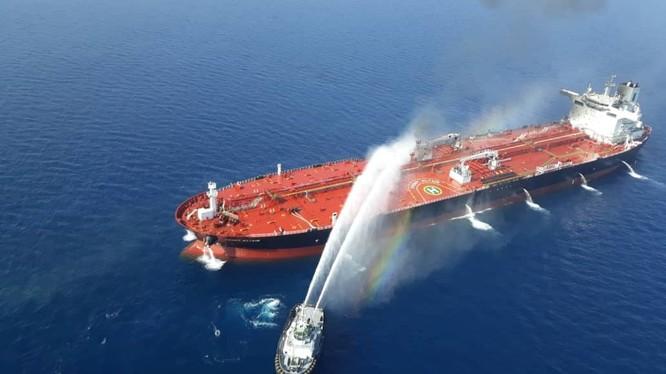 Một tàu của Iran cố gắng dập lửa cho con tàu bị tấn công trên vịnh Oman (Ảnh: Reuters)
