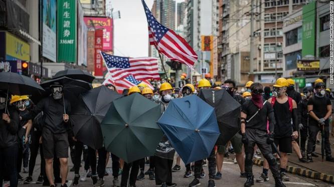 Người biểu tình mang theo cờ Mỹ khi tuần hành ở quận Yuen Long hôm 27/7 (Ảnh: CNN)
