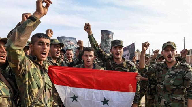 Quân đội chính phủ Syria giơ cao quốc kỳ và ảnh Tổng thống Assad tại ngoại ô thành phố Manbij hôm 15/10 (Ảnh: Newsweek)