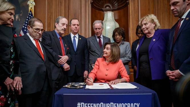 Chủ tịch Hạ viện Nancy Pelosi ký 2 điều khoản luận tội Trump để chuyển cho Thượng viện (Ảnh: Guardian)