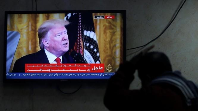 Một người Palestine theo dõi ông Trump tuyên bố kế hoạch hòa bình Trung Đông qua truyền hình (Ảnh: Reuters)