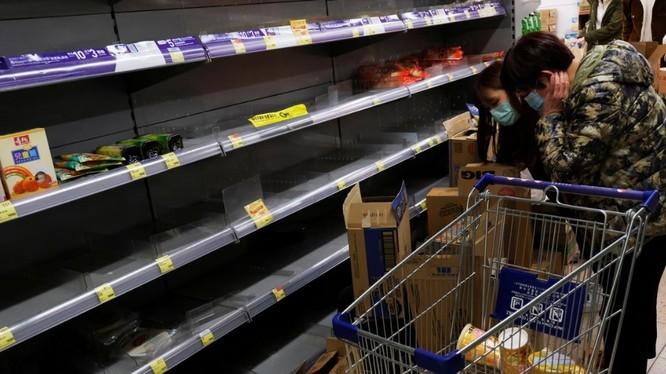 Người tiêu dùng mang khẩu trang đi lung sục các kệ hàng bán mỳ gói để tích trữ (Ảnh: Reuters)