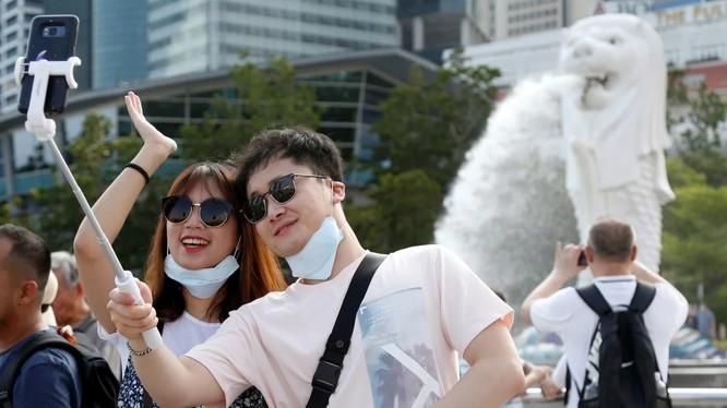 Du khách chụp ảnh tại công viên Merlion, Singapore (Ảnh: SCMP)