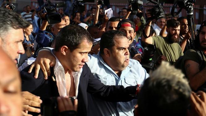 Ông Juan Guaido được hộ tống ra xe để thoát khỏi đám đông người biểu tình ở sân bay (Ảnh: Sputnik)