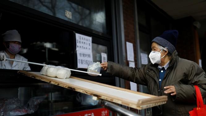 Lo sợ virus corona, người bán hàng ở Bắc Kinh không dám trực tiếp nhận tiền của khách mua (Ảnh: Reuters)