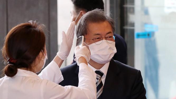 Tổng thống Hàn Quốc Moon Jae-in được đeo khẩu trang và kiểm tra thân nhiệt trước khi vào tòa nhà Quốc hội ở Seoul trong hôm 28/2 (Ảnh: Yonhap)