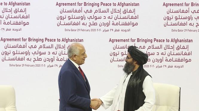 Trưởng đoàn đàm phán của Mỹ, ông Zalmay Khalilzad (trái) và trưởng đoàn đàm phán của Taliban Mullah Abdul Ghani Baradar trong lễ ký thỏa thuận ở Doha (Ảnh: Politico)