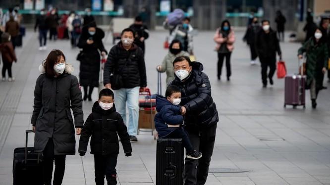 Nhiều hành khách mang khẩu trang chống COVID-19 tại trạm đường sắt ở Bắc Kinh (Ảnh: AFP)
