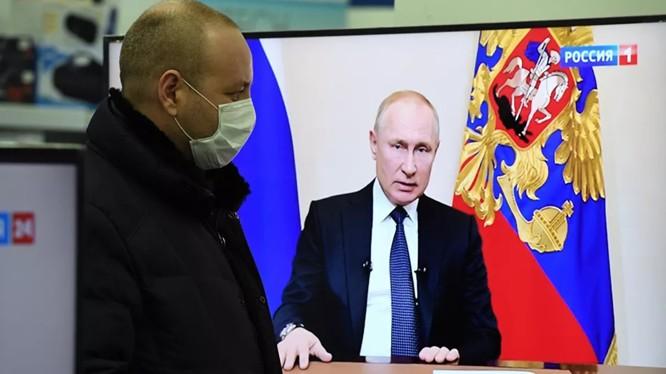 Một người dân theo dõi ông Putin phát biểu trên truyền hình (Ảnh: Sputnik)