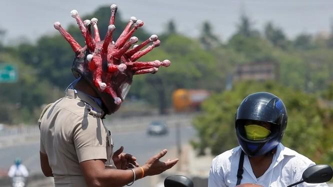Cảnh sát ở thành phố Chennai đội mũ tạo hình giống virus corona để thực thi lệnh phong tỏa trong đại dịch COVID-19 (Ảnh: Reuters)