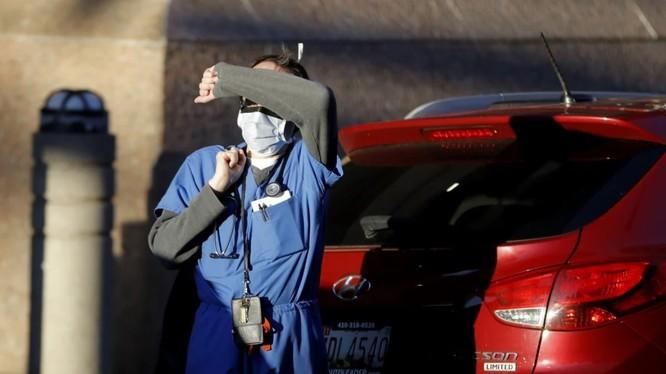 Nhân viên thuộc Trung tâm Y tế Baltimore, bang Maryland, Mỹ che mắt khỏi ánh nắng (Ảnh: AP)