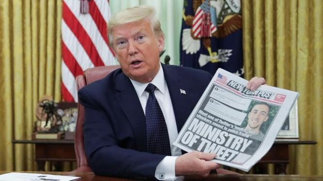 Tổng thống Trump cầm tờ New York Times lúc phát biểu trước phóng viên trong khi chuẩn bị ký sắc lệnh mới (Ảnh: Reuters)