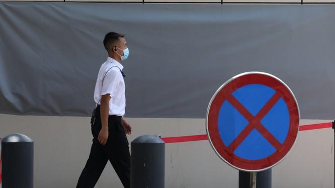 Một nhân viên an ninh băng qua tấm biển cấm vào bên ngoài tòa lãnh sự quán Mỹ ở Thành Đô (Ảnh: SCMP)