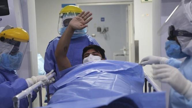 Một bệnh nhân được chuyển ra khỏi khu điều trị đặc biệt ở Lima, Peru (Ảnh: AP)