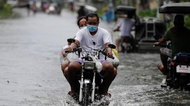Một người đàn ông lái xe máy trong lúc bão Molave đổ bộ vào tỉnh Pampanga của Philippines (Ảnh: AP)
