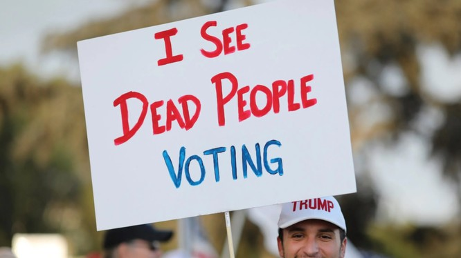 """Một người ủng hộ Trump giơ tấm biển với dòng chữ: """"Tôi thấy người chết đi bỏ phiếu"""" (Ảnh: Telegraph)"""