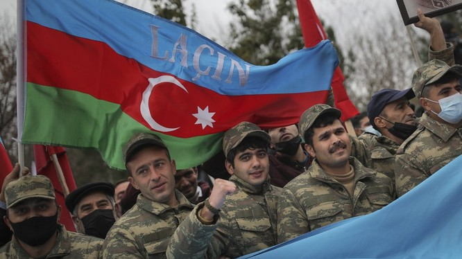 """Binh sĩ Azerbaijan giơ cao lá quốc kỳ bên trên có dòng chữ """"Lachin"""" để ăn mừng chiến thắng (Ảnh: AP)"""
