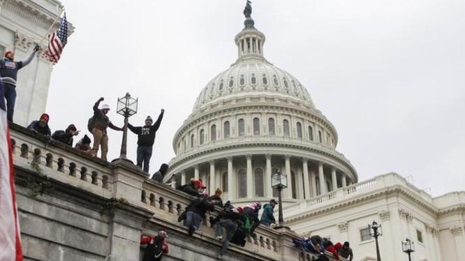 Người biểu tình trèo lên tường tòa nhà Quốc hội Mỹ hòng thâm nhập vào bên trong (Ảnh: Reuters)