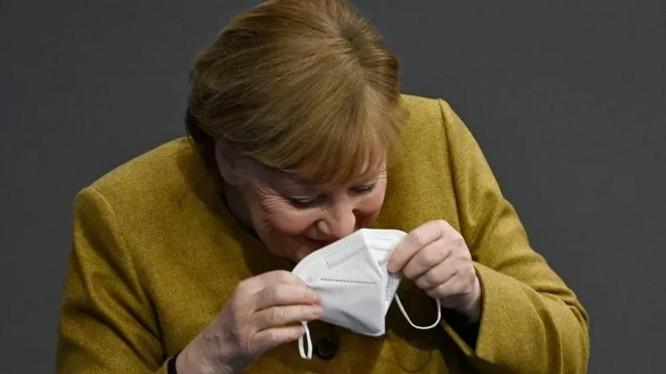 Bà Merkel nhịn cười khi đang đeo lại khẩu trang của mình (Ảnh: Getty)