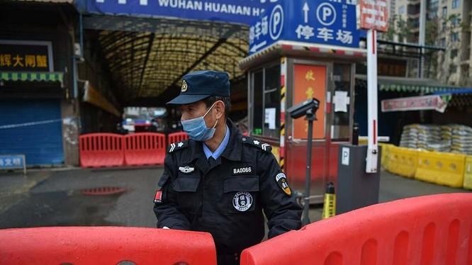 Một nhân viên bảo an đứng giám sát bên ngoài chợ hải sản Hoa Nam (Ảnh: AFP)