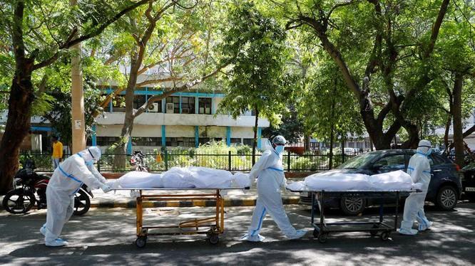 Nhân viên y tế mặc thiết bị bảo vệ cá nhân (PPE) khiêng thi thể của những người nhiễm COVID-19 (Ảnh: Reuters)