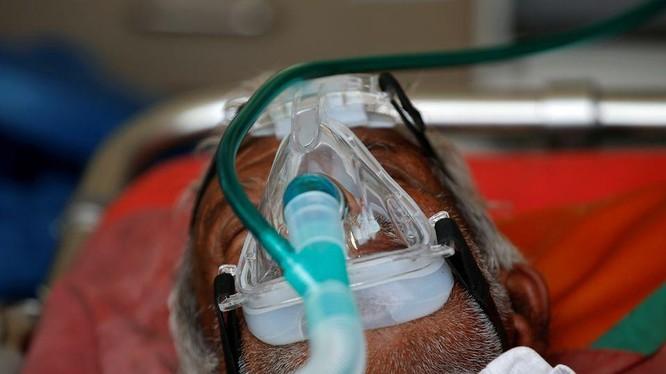 Một bệnh nhân được cho thở bình oxy trong xe cấp cứu, chờ được nhập viện điều trị COVID-19 (Ảnh: Reuters)