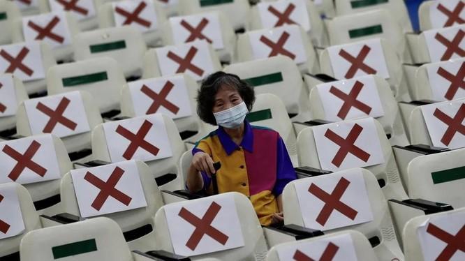 Một người dân ở Đài Loan ngồi chờ 15 phút sau khi được tiêm vaccine COVID-19 (Ảnh: EPA)