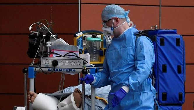 Một nhân viên y tế Anh chăm sóc bệnh nhân Covid-19 (Ảnh Reuters)