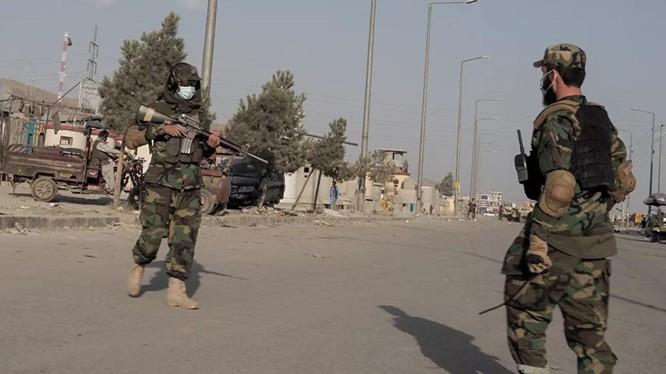 Chiến binh Taliban đứng gác một con đường dẫn tới sân bay Kabul (Ảnh: Reuters)