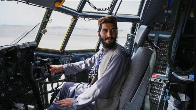 Chiến binh Taliban ngồi trên một chiếc máy bay quân sự mà Mỹ bỏ lại sau khi rút khỏi sân bay Kabul (Ảnh: AFP)