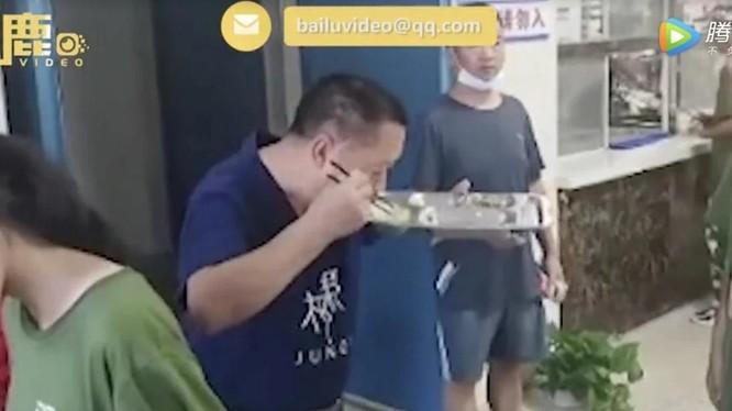 Ông Wang ăn lại đồ thừa của học sinh (Ảnh: Baidu)