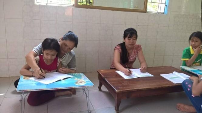 Mẹ Thúy (bìa trái) dạy các con học.