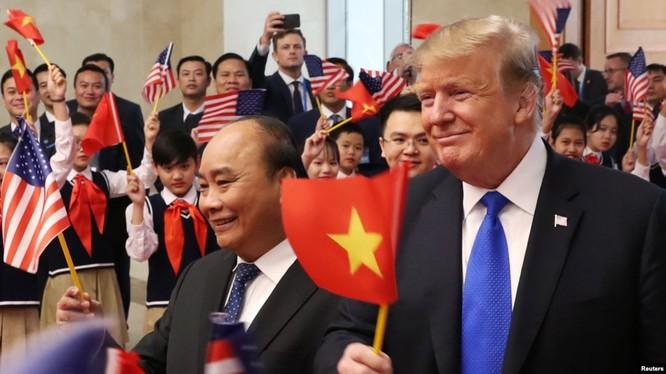 Tổng thống Mỹ Donald Trump và Thủ tướng Việt Nam Nguyễn Xuân Phúc vẫy cờ khi được các em học sinh chào đón tại trụ sở Văn phòng Chính phủ ở Hà Nội, ngày 27 tháng 2, 2019. (Ảnh: Tư liệu)