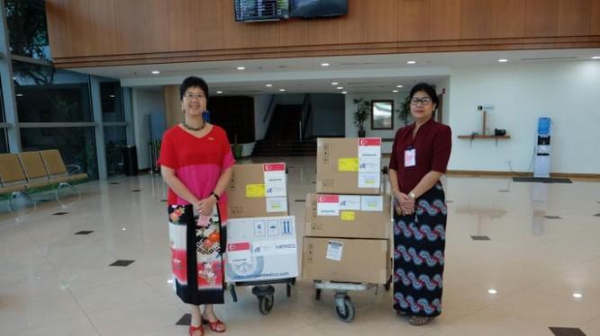 Đại sứ Singapore tại Myanmar - Vanessa Chan (trái) bàn giao các vật tư y tế tài trợ của Singapore cho Giám đốc Phòng thí nghiệm Y tế Quốc gia Myanmar - Htay Htay Tin, bao gồm 3.000 bộ xét nghiệm chẩn đoán và hai máy phản ứng chuỗi Polymerase (PCR) để xét