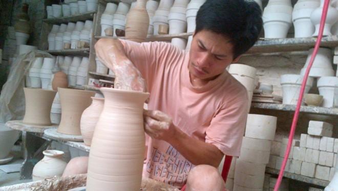 Nghệ nhân Hà Nội Phạm Anh Đạo bên bàn xoay với một sản phẩm gốm được làm theo phương pháp cổ truyền: vuốt- nặn- vẽ- Ảnh nhân vật cung cấp.