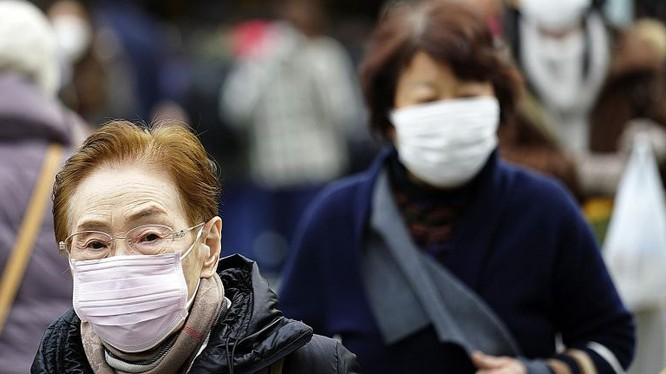 Người dân đeo khẩu trang để phòng bệnh khi ra đường. Ảnh: ASSOCIATED PRESS