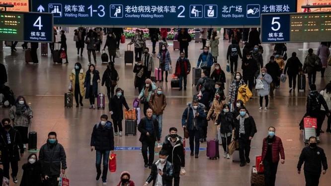 Người dân đeo mặt nạ khi đi du lịch vào dịp lễ năm mới tại nhà ga phía Tây Bắc Kinh, Trung Quốc. Ảnh: AFP